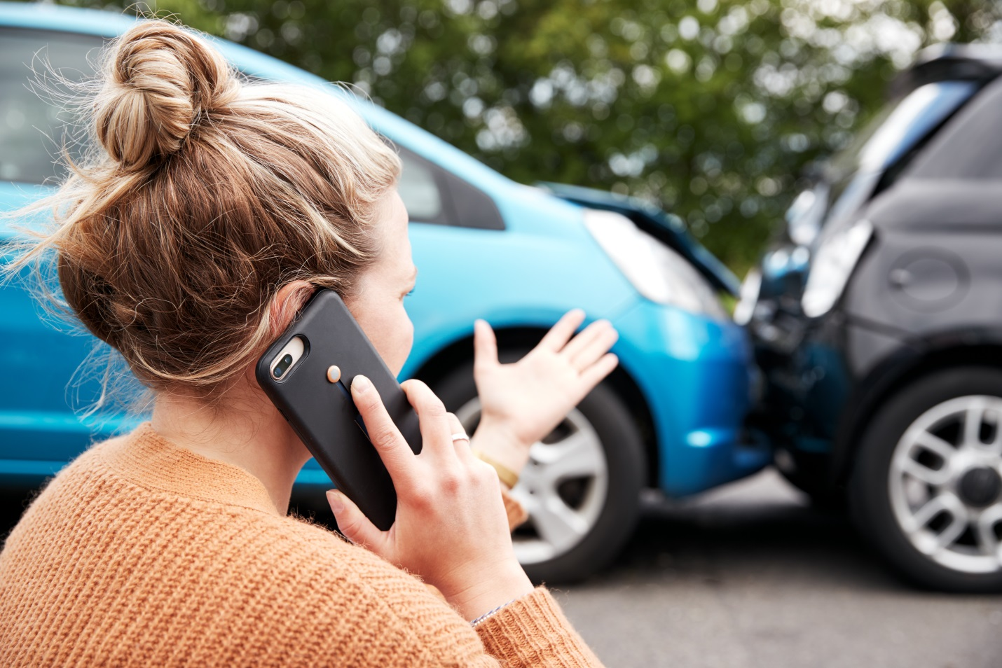 woman talking on phone over a car collision